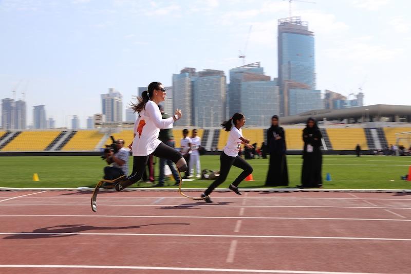 Nella fotografia, Giusy corre sulla pista di Doha nella Giornata dello Sport Paralimpico
